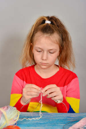 Girl in a striped sweater learning to knit with a serious face.