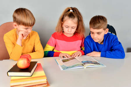 Two brothers and sister are reading a book on a white table. Stockfoto