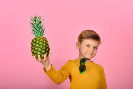 A boy in sunglasses holds a pineapple in his right hand.