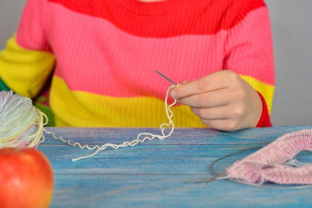 Girl sitting at a table with an apple and learning to knit.