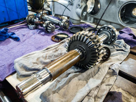 The gear wheel on the shaft from the gearbox in disassembled form for repair in a workshop