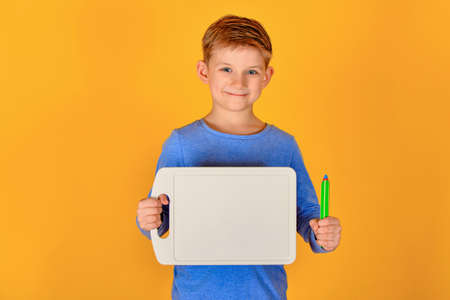 A boy on a yellow background holds a pencil in one hand, and in the other a place for an advertising inscription