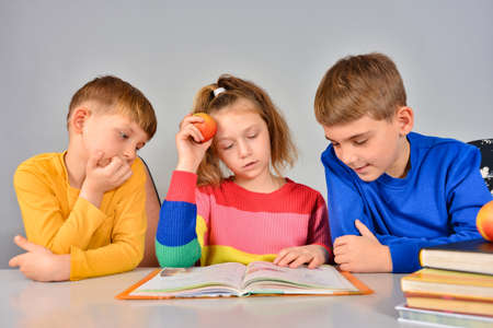Two brothers and sister are reading a book on a white table. Reklamní fotografie