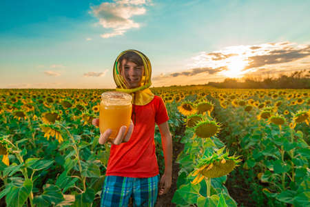 A boy wearing a mask from bees holds out in his hand a bee product in a jar among a field of sunflower.