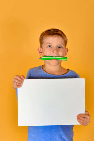 A boy stands with an empty white board and holds a pencil in his mouth.