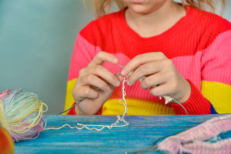 A girl sits at a table and tries to learn how to knit herself.