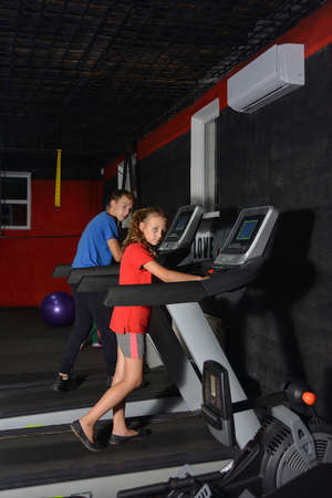 Brother and sister perform cardio exercises on a treadmill in the gym.