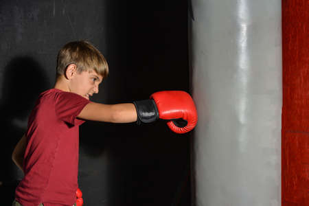 A teenage boy angrily punches a sports bag in the gym. Reklamní fotografie