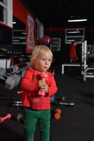 A small child holds a dumbbell in his hands. Little girl goes in for sports in the gym. Reklamní fotografie
