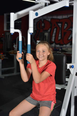 The girl performs an exercise on the simulator in the gym. Reduction of hands in the machine, pumping of the pectoral muscles.