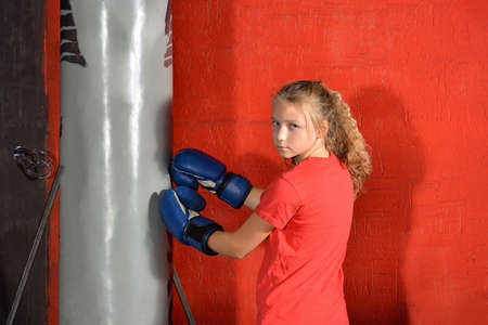 A girl in boxing gloves is practicing blows on a hanging bag. Reklamní fotografie
