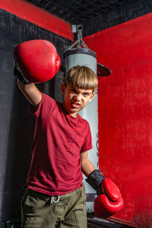 A teenage boy in boxing gloves angrily swings his fist for a blow.