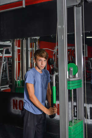 Boy teenager performs triceps exercise on the simulator in the gym. Health care from childhood.