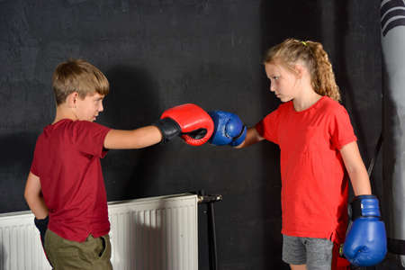 Brother and sister in boxing gloves greet each other by banging their fists. Children are boxing.