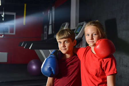 Brother and sister in boxing gloves are hugging each other. Children are boxing. Reklamní fotografie