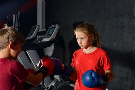 Boy and girl in boxing gloves are boxing with each other in the gym. Children are boxing.