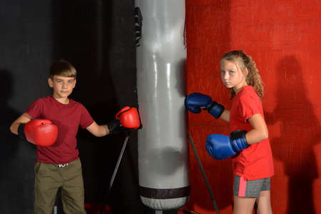 A boy and a girl in boxing gloves hit the hanging sports bag and look into the camera.