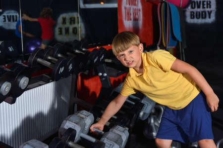 A preschooler boy is trying to lift a heavy and large dumbbell in the gym. The child goes in for sports in the gym. Stockfoto