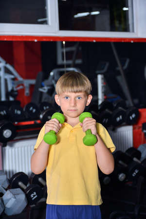 Preschooler boy holds dumbbells in his hands. The child goes in for sports in the gym.