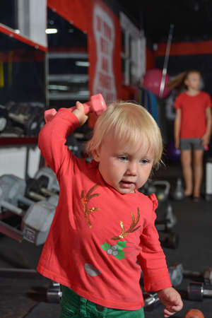 A small child in the gym raises a dumbbell up. Little girl goes in for sports.