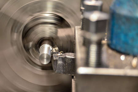 Working on a lathe, a cutter removes chips from the workpiece surface being processed