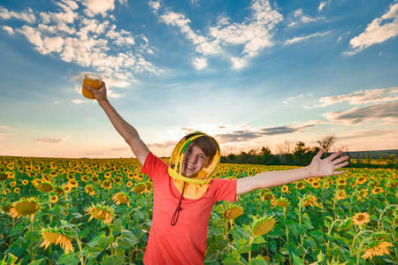 A joyful guy in a beekeeper mask holds honey in his hand against the background of a field with sunflowers and the evening sky. Beekeeping concept.