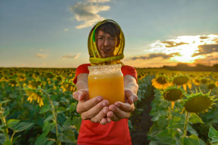 The guy holds a jar of honey on his outstretched hand and offers it against the background of a field with sunflowers and the evening sky. Beekeeping concept.