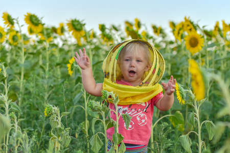 A joyful little girl dressed in a beekeeper's mask waves her hands against the background of a field with sunflowers. Beekeeping concept. Stockfoto