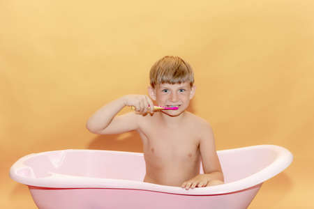 A small child brushes his teeth while sitting in the bathroom, on a yellow background. Stockfoto