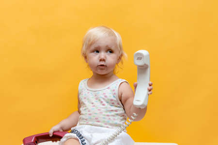 A small child plays with an old corded telephone. Stockfoto