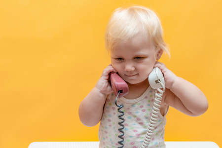 A little girl holds in her hands a tube from a wired telephone and looks around. Stock fotó