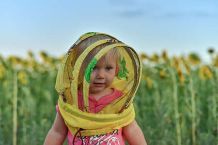 Surprised little girl wearing a beekeeper mask against the backdrop of a field with sunflowers. Beekeeping concept.