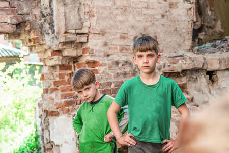 Two sad and unhappy brothers in a destroyed and abandoned building, staged photo.
