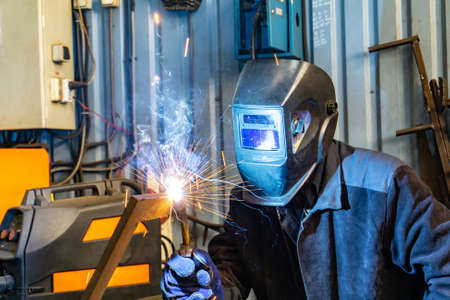 An electric and gas welder in an electromechanical workshop welds a metal structure at a mechanical assembly site