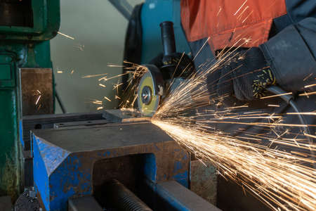 Hand sander at work, sparks from the cutting wheel