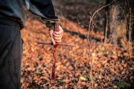 A man holds in his hand a bloody wooden cross that drives out demons. Worship and sacrifice to god