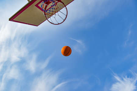 A basketball ball flies into a hoop with a net against a blue cloudy sky. Sports activities on the playground Imagens