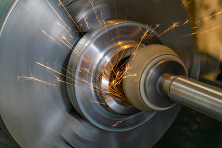 High-precision finishing of the part by grinding with a face abrasive wheel on a cylindrical grinding machine. Stockfoto