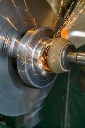 Grinding the end of the workpiece with an abrasive wheel on a circular grinding machine. Imagens