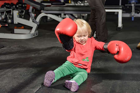 Little girl in boxing gloves sits on the floor of the gym.