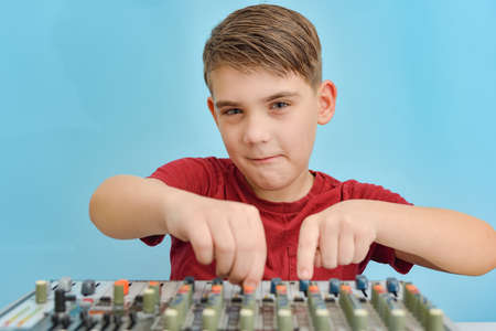 A boy adjusts the equalizer of a mixing console in a music studio.