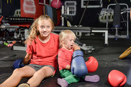 A girl and her younger sister put on boxing gloves at the gym.