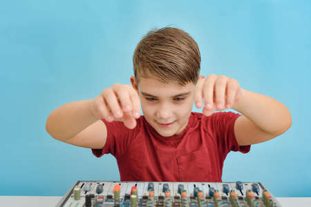 An enthusiastic child is about to tune a music mixing console.