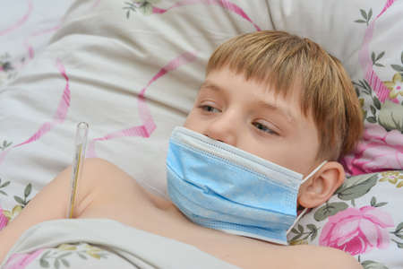 A sick child in a mask lies in bed in home quarantine.