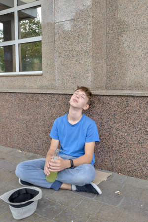A drunken teenager beggar sits with a drink in his hand and begs for money. Teenage alcoholism concept.