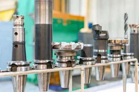 Accessories and tools for a CNC machine on a rack for equipment at a factory and enterprise. Imagens