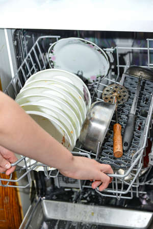 Housewife girl puts dirty dishes in the dishwasher for washing and cleaning from food.