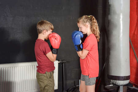 A boy and a girl in boxing gloves greet each other before a fight among the gym. Imagens