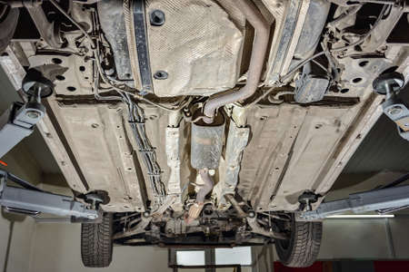 Car on a lift to inspect the repair of a faulty part, bottom view. Imagens