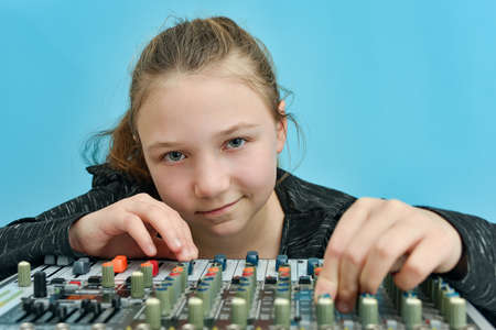A girl adjusts the equalizer of a mixing console in a music studio.